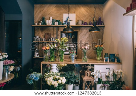 Small business. Flower shop interior. Floral design studio, decorations and arrangements and gifts. Flowers delivery service and sale of home plants in pots, wooden showcase, nobody.