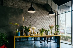 Small business. Flower shop loft modern interior. Floral design studio, decorations and compositions, gifts. Flower delivery and sale of indoor plants in pots, showcase, nobody.