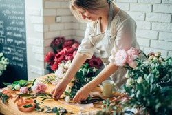 Small business. Male florist unfocused in flower shop. Floral design studio, making decorations and arrangements. Flowers delivery, creating order