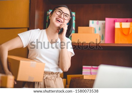 Small business owner, Asian woman hold package box, using mobile phone call receiving purchase order, working at home office. Online marketing delivery, startup SME entrepreneur or freelance concept.