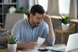 Small business owner experiences financial crisis, high costs, bank debt, money overspend concept. Man sitting at desk looks at laptop screen holding receipt feels desperate after calculating expenses