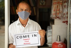 Small business owner in medical mask holding Wellcome notice infront of door after store reopening during coronavirus or covid-19 - concept of support local business and restart work after pandemic.