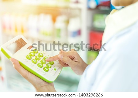 Small business owner or entrepreneur using a calculator in her hand, calculating financial expense at home office or grocery expenses budget or pharmacy and tax after startup new business #1403298266