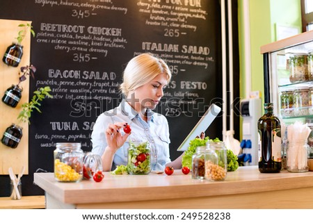 Small business owner reading the recipe on a digital tablet