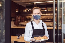 Small business owner smiling and standing at entrance of open restaurant while reopening after lockdown quarantine – Successful entrepeneur opening store activity - support local businesses.