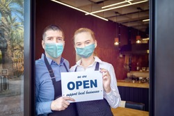 Small business owner smiling while holding sign for reopening of restaurant after lockdown quarantine due to coronavirus - Entrepeneur open coffee shop activity to support local businesses.