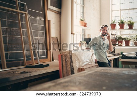 Small business owner talking on his phone while smiling and standing casually in his studio workshop
