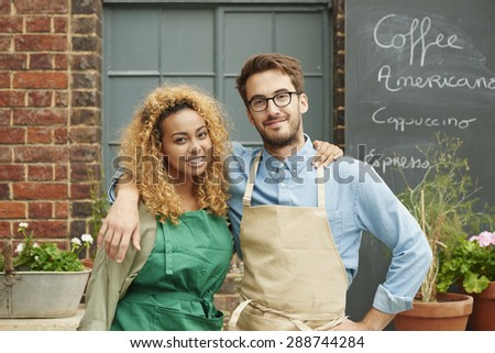 Small business owners standing in front of cafe wearing aprons portrait cafe ready for work