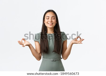 Small business owners, women entrepreneurs concept. Relaxed and peaceful smiling asian businesswoman feeling relieved after taking antidepressants, meditating, doing yoga exercise Foto stock ©