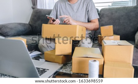Small business parcel for shipment to client at home, Young entrepreneur SME freelance man working online business by using smart phone with making on purchase order and preparing package product.