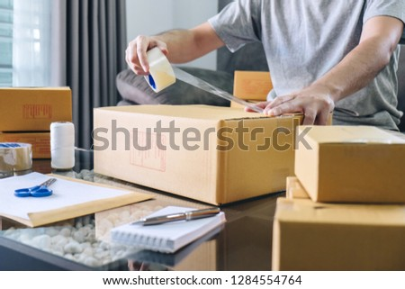 Small business parcel for shipment to client, Young entrepreneur SME freelance man working with packaging their packages box delivery online market on purchase order and preparing package product.