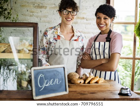 Small business partnership women friends at bakery shop smiling together