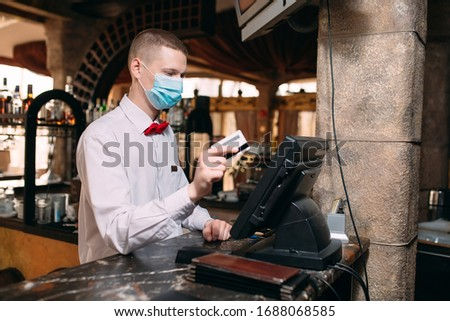 small business, people and service concept. man or waiter in medical mask at counter with cashbox working at bar or coffee shop