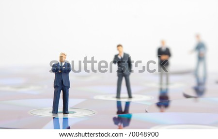 Small business people standing on computer CDs