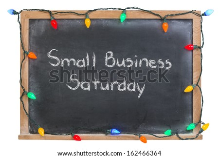 Small Business Saturday written in white chalk on a black chalkboard surrounded by festive colorful lights isolated on white