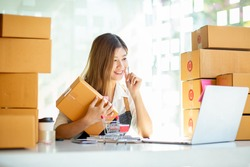 Small Business SME entrepreneur of Young Asian women working with laptop for Online shopping at home,Cheerful and Happy with box for packaging in home,Own Business Start up for Online shopping
