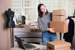Small business, tailor shop, costume designer's workshop. A young female entrepreneur in the workplace, packing parcels and running an online store. Portrait in the interior