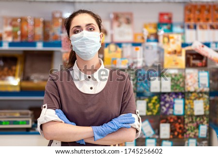 Small businesses during the pandemic.Portrait of a female worker in a medical mask and gloves posing with her arms crossed.Grocery store on the background.Concept of protection against coronavirus Foto stock ©