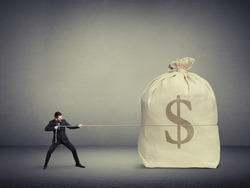 small businessman pulling the rope a big bag of money over dark background
