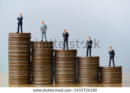 Small businessmans figures standing on tstack of coins. Time is money. Time investment and retirement saving. 401K. Business finance.