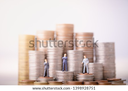 Small businessmans figures standing on turning poing. The concept of role conflict in society. money saving and Investment concept. Business finance. Inequality and social class.