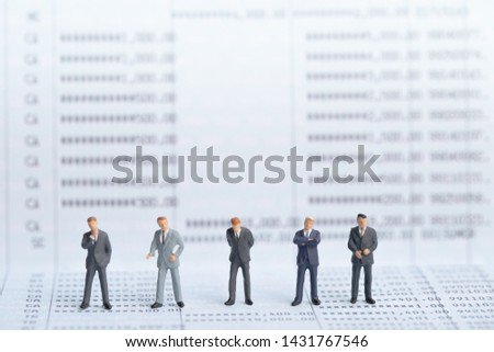 Small businessmans figures standing on turning point on bank passbook. Money saving and Investment concept. Business finance. Business teamwork. #1431767546