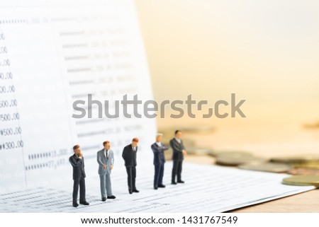 Small businessmans figures standing on turning point on bank passbook. Money saving and Investment concept. Business finance. Business teamwork. #1431767549