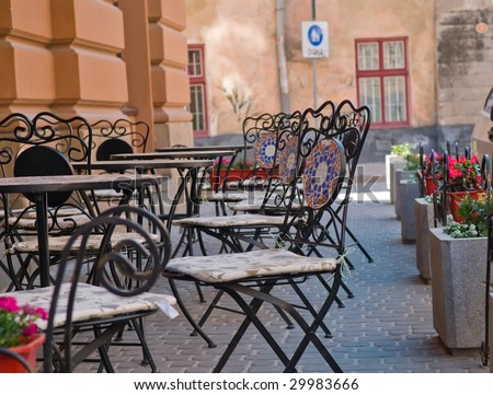Small cafe in the street an old city. Tables and beautiful chairs on sidewalk.