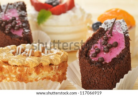 Small  cakes  with cream and  berries on bamboo table cloth