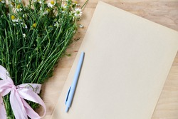 Small camomiles bouquet tied with pink ribbon and beige paper sheet with light blue pen on wooden table. Natural background with wild flowers. Ecological texture for poems, letters, romantic notes.