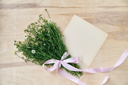 Small camomiles bouquet tied with pink ribbon and beige vintage eco paper sheet on wooden table. Natural background picture of wild flowers. Ecological texture for poems, letters, romantic notes.
