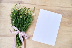 Small camomiles bouquet tied with pink ribbon and white paper sheet on wooden table. Natural background picture of wild flowers. Ecological texture for poems, letters, romantic notes.