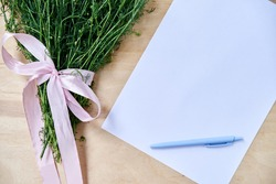 Small camomiles bouquet tied with pink ribbon and white paper sheet with light blue pen on wooden table. Natural background with wild flowers. Ecological texture for poems, letters, romantic notes.