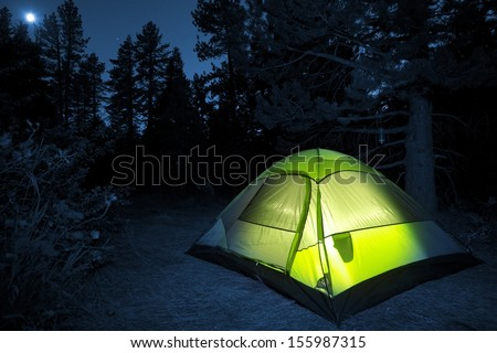 Small Camping Tent Illuminated Inside. Night Hours Campsite. Recreation and Outdoor Photo Collection.