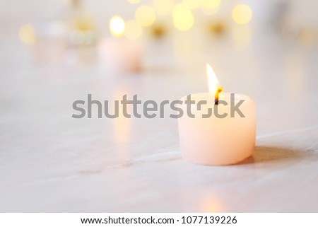 Small candle with light yellow spots on light background #1077139226