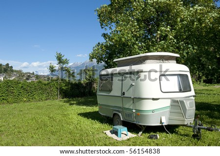 Small caravan at a camping with at background mountains with snow