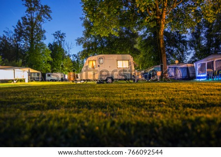 small caravan on a campsite at night. Camping holiday in the outdoors. Beautiful family holiday in Switzerland. Camping car in the wood.