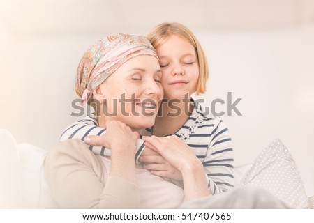 Small caring child embracing her ill mother with headscarf