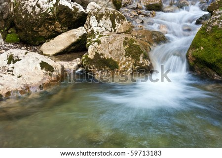 Small cascade and flowing water and moss on rocks