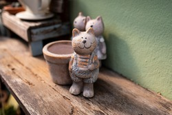 Small Cat sculpture with garden pot on the wooden floor