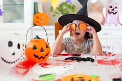 Small caucasian child in witch hat having fun while making some Halloween pumpkins by hand. She is in the living room.