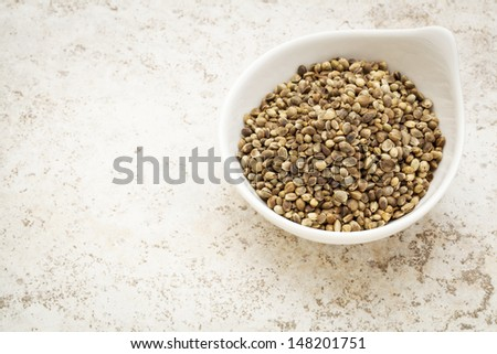 small ceramic bowl of  dry hemp seeds against a ceramic tile background with a copy space