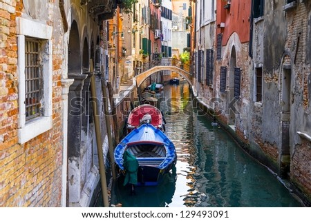 Small channel in Venice, Italy with boats parked around.
