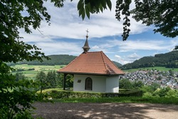 Small chapel on a mountain in the background a small village