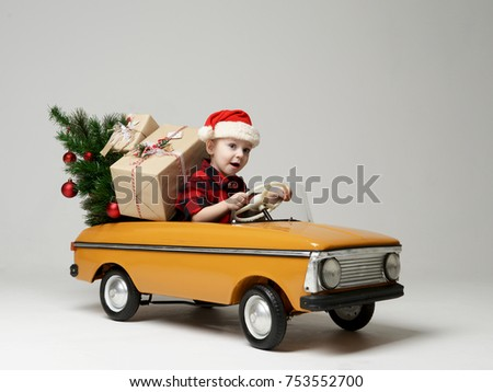Stock Photo Small child boy in winter sitting in a yellow  retro toy car pulls on Christmas tree decorated on grey background