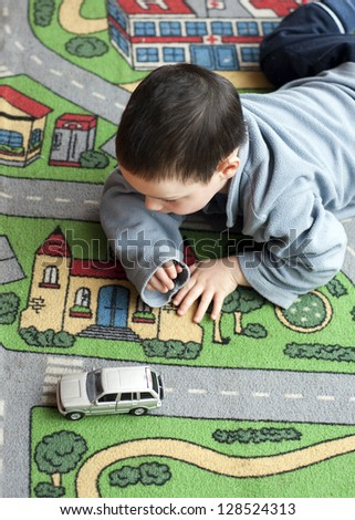 Small child boy playing on a road themed carpet with a toy car..