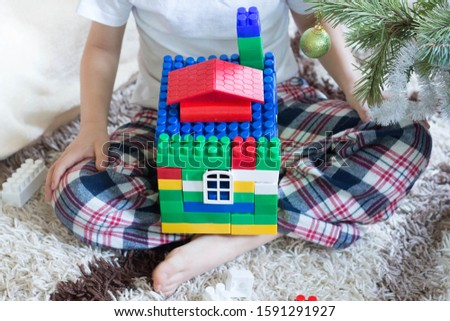 Small child builds a house of plastic blocks at new year tree. Childhood and educational concept.Leisure time activity.Christmas time.