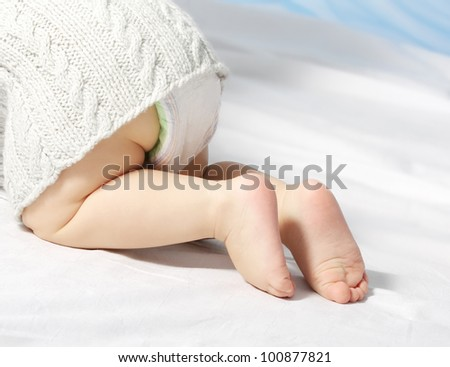 small child funny creeps, legs largely, on white