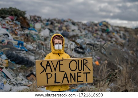 Small child holding placard poster on landfill, environmental pollution concept. Zdjęcia stock ©