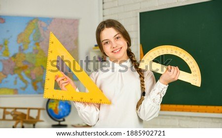 Small child holding ruler for mathematics lesson. Mathematics matters. Cute little schoolgirl with geometrical tool for mathematics. Science and Technology. Elementary school mathematics or maths.